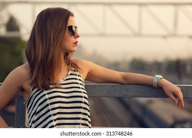 Lonely girl standing on the bridge. Toned image