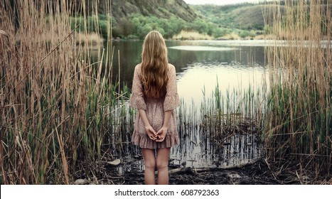 Lonely girl standing in reeds at the river