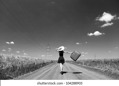 Lonely girl with suitcase at country road. Photo in black and white color style.