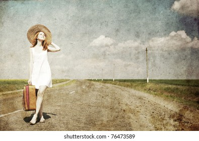 Lonely girl with suitcase at country road.Photo in old image style.