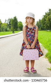 Lonely girl with suitcase standing on road and waiting a bus
