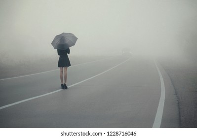 A lonely girl with an umbrella is on the road and waiting