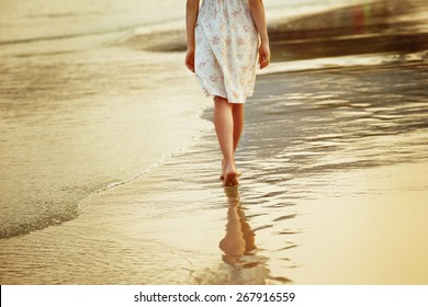 A lonely girl is walking along island coastline and has reflection on wet sand.