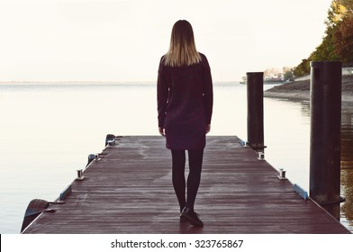 lonely girl walking on the pier. Free space for text. Copy space