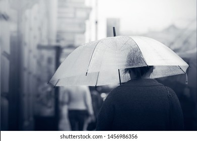 A lonely girl walks along a city street in foggy weather under a transparent umbrella that protects her from the rain. Black and white color adds a sad melancholic mood.
