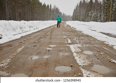 A lonely girl walks along a dirty gravel road into the distance to the horizon, on the roadsides lies snow, winter.
