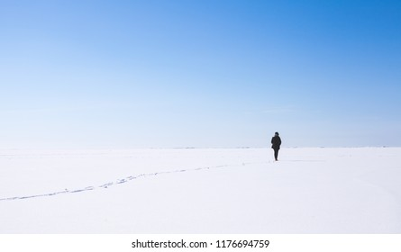 Lonely girl walks along the endless snowfield, Russian winter landscape
