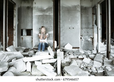 A lonely girl in a white T-shirt and jeans sits on the ruins of a ruined house. Sad expression, tragic atmosphere