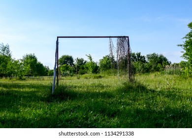 Lonely goal in neglected and overgrown soccer court among grass vegetation.
