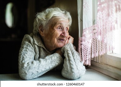 Lonely grandma. Old woman looks out the window.
