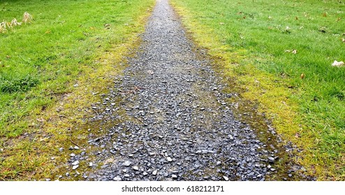 lonely, gravel macadam footpath with grass on either side
