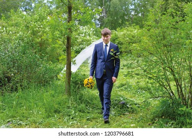 The lonely groom in a blue suit goes through the park, holds the wedding bouquet in his hand. Veil on the head of the groom. Looking for a runaway bride or groom. Wedding ceremony same-sex couple.