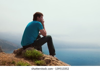 Lonely guy looking into the distance at sea