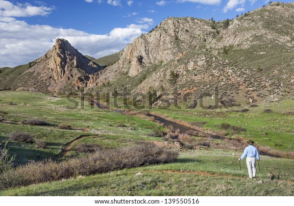 lonely hiker contemplating mountain vista  in springtime- Eagle Nest Open Space near Fort Collins, Colorado