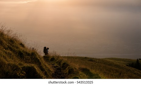 Lonely hiker walking up a mountain at sunrise