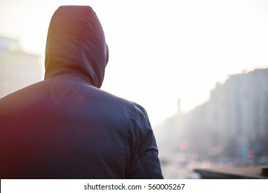 Lonely hipster man in hood walking on city street in the evening