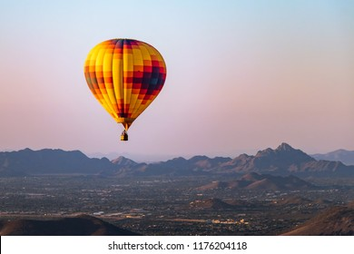 A lonely hot air balloon flies over Phoenix Arizona with the Sonoran Desert in the background.