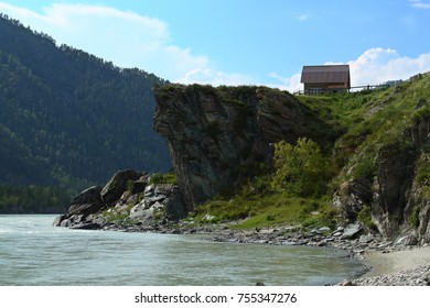 A lonely house on the shore of a mountain river Katun.