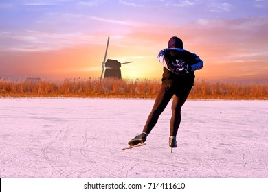 Lonely ice skater in the countryside from the Netherlands at sunset