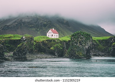 Lonely icelandic house with red roof on the sea coast with green grass meadow, rocks anf foggy sky. Natural Iceland travel landscape.