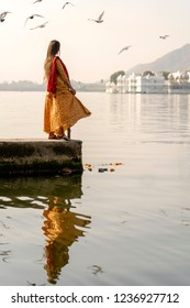 Lonely indian woman in a beautiful dress looks at the lake in Udaipur, Rajasthan, India. Close up