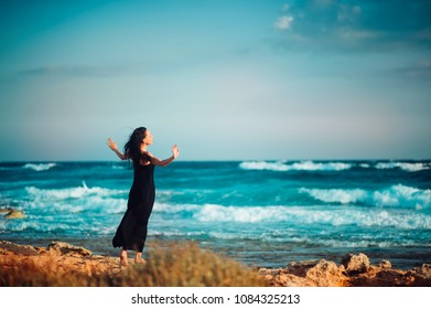 Lonely inspired woman in black dress staying on seaside dreaming and looking to sea on windy sunset day. Back view. Emotions loneliness Lifestyle Solitariness concepts
