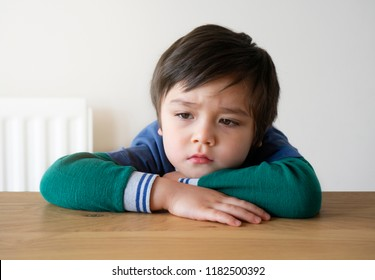 Lonely kid boy sitting alone and looking down with bored face,Closeup preschool child with unhappy or sad face,Head shot of bored 5 years old boy,Child laying head down on his arms with thinking face.