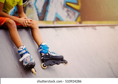 lonely kid sitting in park. skate park scene. boy legs with in line skates. spare time