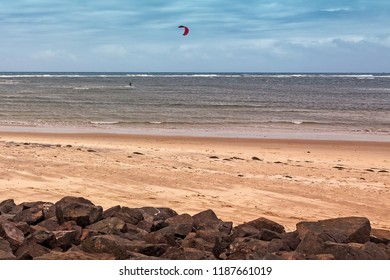 A lonely kite surfer on a cloudy day at a beach in Caloundra, Queensland, Australia.  On a sunny day the beach would be packed with people.