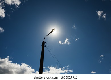 A lonely lamppost on the background of the daytime cloudy sky. The sun is located directly behind the lamp.