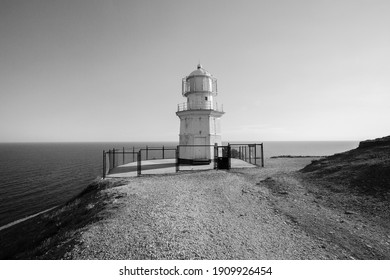 Lonely lighthouse by the sea. Black and white photo.
