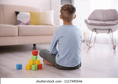 Lonely little boy with cubes sitting on floor at home. Autism concept