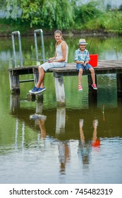 Lonely little boy with his sister fishing on river on the summer day