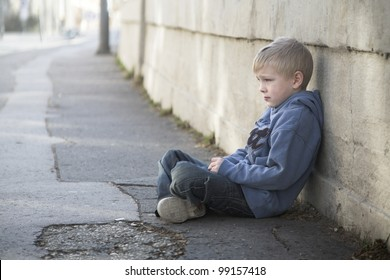 Lonely little boy sits at pathway