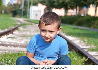 lonely little boy sitting on a rails