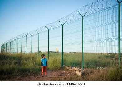 lonely little caucasian kid refugee watching at high fence with barbed razor wire desert