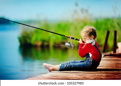 lonely little child fishing from wooden dock on lake