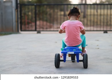 Lonely little girl at home. Children riding a old tricycle on road. Three-wheeled vehicle. Spin the tricycle alone.
