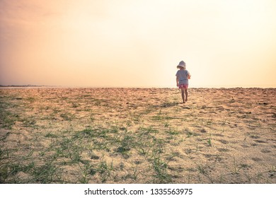 Lonely lost child toddler standing alone in sand dunes exploring childhood travel lifestyle