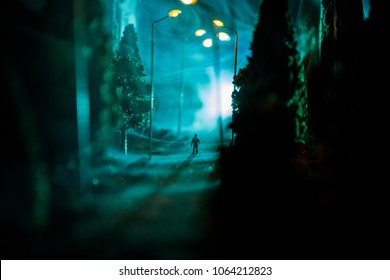 Lonely man. City at night in dense fog. Thick smog on a dark street. Silhouettes of man on road. Table decoration. Selective focus