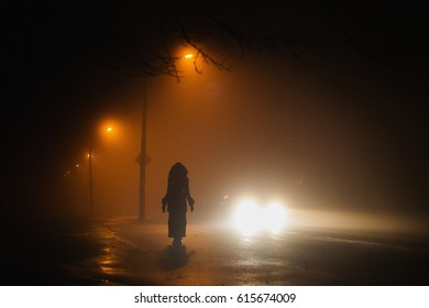 Lonely man. City at night in dense fog. Thick smog on a dark street. Beautiful mixed lighting from windows. Silhouettes of people and trees. Pillars at road
