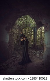Lonely man in a cloak composing music, playing violin in an old abandoned castle