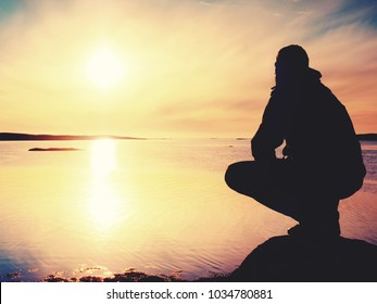 Lonely man hiker sits alone on the rocky  coast and  enjoying sunset. View over rocky cliff to free ocean