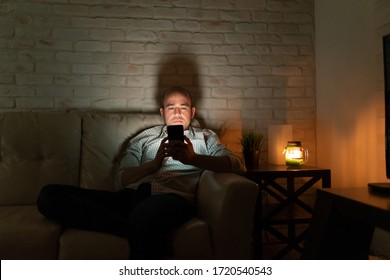 Lonely man in his 30s sitting on a couch at home and looking at his smartphone at night