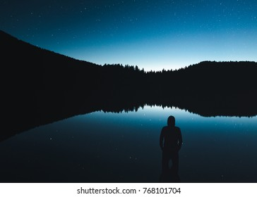 Lonely man at the lake under the stary sky. Laghi di Fusine, Julian Alps, Italy, Europe.