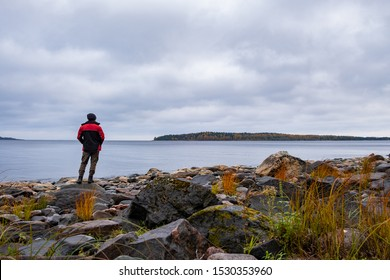 lonely man looks at the pristine nature of the North. The lifestyle of the Hiking traveler in the cold season