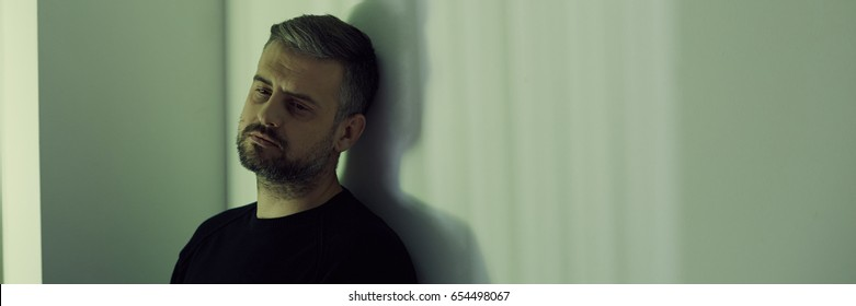 Lonely man missing his wife, standing against wall, panorama
