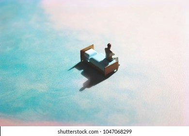 Lonely man on a dreamy, cloud-like background on a bed. Floating miniature figure in a dreamscape of blue and pink.
