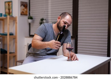 Lonely man pouring wine in glass from bottle drinking alone feeling depressed and unhealthy. Miserable adult with alcohol addiction being intoxicated with liquor, booze, beverage