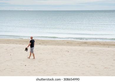 Lonely man relax walking along the sea beach seashore